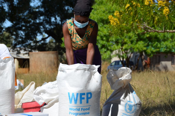 A WFP beneficiary divides shares of WFP food assistance at a distribution in Bindura district, Zimbabwe. Photo: WFP/Tatenda Macheka
