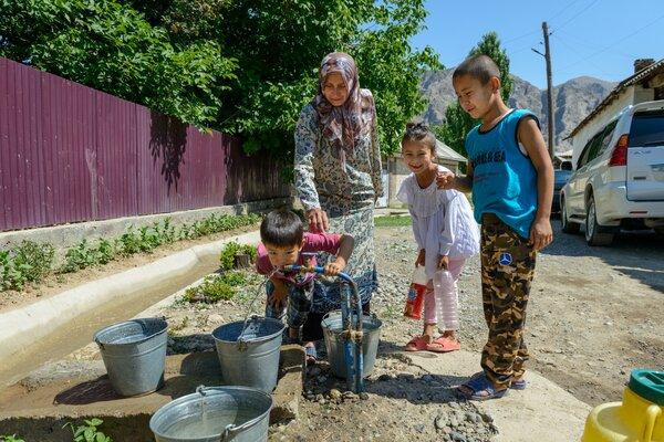 夏の気温が50°Cにも達するキルギスの最も暑い地域に新しく設置された水道管を使う家族。 WFP/Maksim Shubovich