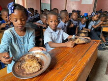 Photo: WFP/Alexis Masciarelli, primary school children eat their hot meal in their classroom at the Catherine Flon state school, in the city of Jeremie, Haiti.