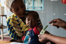 WFP/Arete/Fredrik Lerneryd. WFP staff, Francis Mpoyi, measures baby's arm during a routine check-up in Kalemie, Democratic Republic of Congo on 19th February 2021.