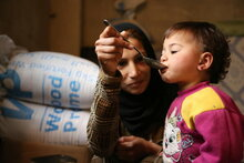 Photo: WFP/Abeer Etefa, Woman displaced with her family from Douma in rural Damascus to Adra - feeding her 18 month old daughter lunch.